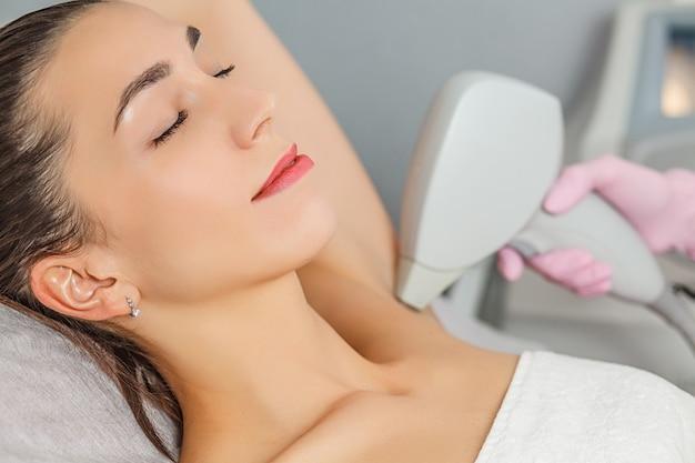La depilación láser. primer plano de esteticista quitando el vello de la axila de la mujer joven Foto Premium