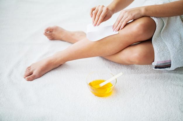 Depilación. piernas depilatorias con cera y cinta adhesiva. Foto Premium