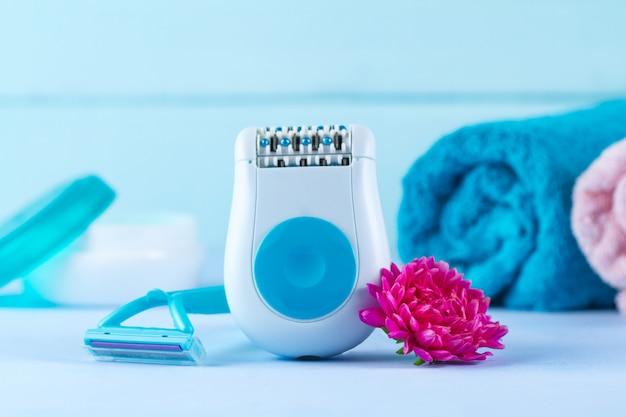 Depiladora, crema, navaja de afeitar, toallas y una flor. depilatorio. eliminación de vello no deseado. concepto de depilación Foto Premium