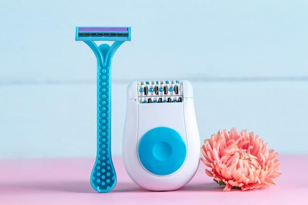Depiladora, maquinilla de afeitar para mujer y una flor rosa. depilatorio. eliminación de vello no deseado. concepto de depilación Foto Premium