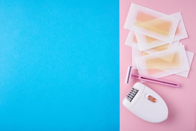Depiladora, navaja y tiras de cera en azul y rosa Foto Premium