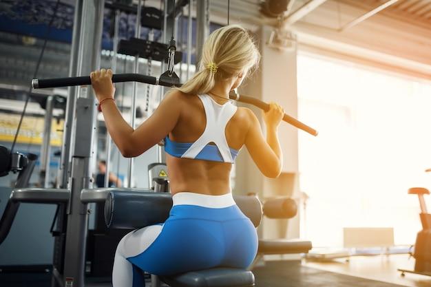 Deportes hermosa mujer joven posando en el gimnasio. Foto Premium
