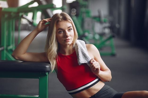Deportes mujer rubia en ropa deportiva descansar en un gimnasio Foto gratis