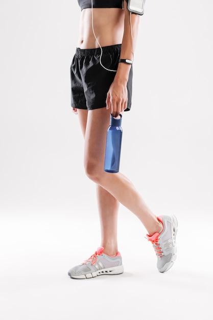 Deportista en auriculares con botella de agua Foto gratis