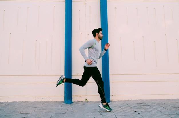 Deportista corriendo cerca de la pared Foto gratis