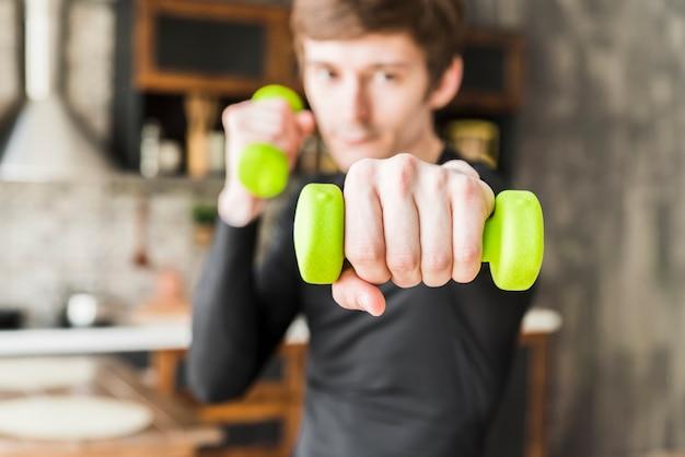 Deportista enfocado en entrenamiento con pesas pequeñas Foto gratis