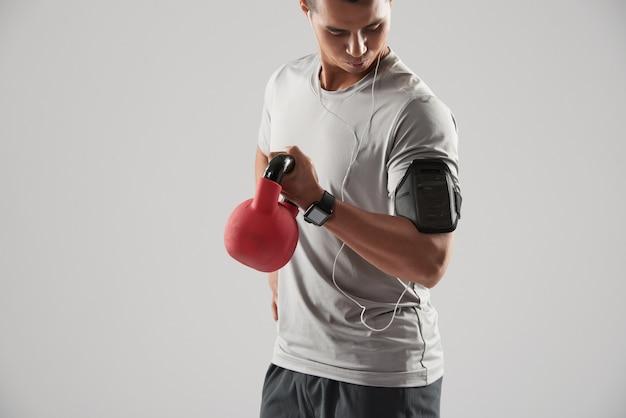 Deportista haciendo ejercicio de bíceps con pesas rusas Foto gratis