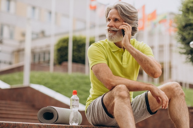 Deportista de mediana edad sentado en las escaleras con teléfono Foto gratis