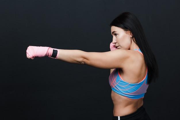 Deportista muay thai mujer fuerte boxeadora posando en estudio de  entrenamiento en fondo negro | Foto Premium