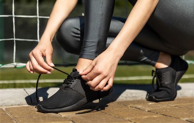 Deportiva chica atando sus zapatillas al aire libre Foto gratis