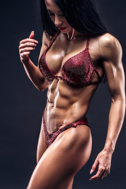 Deportiva jovencita bronceada sexy con grandes músculos abdominales Foto Premium