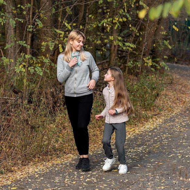 Deportiva madre e hija corriendo en la naturaleza Foto gratis