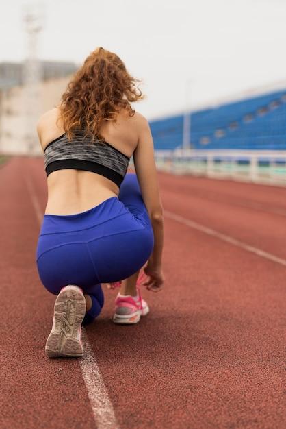 Deportiva mujer ata sus cordones de zapatos Foto gratis