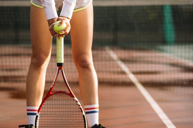 Deportiva mujer descansa sobre la raqueta de tenis Foto gratis