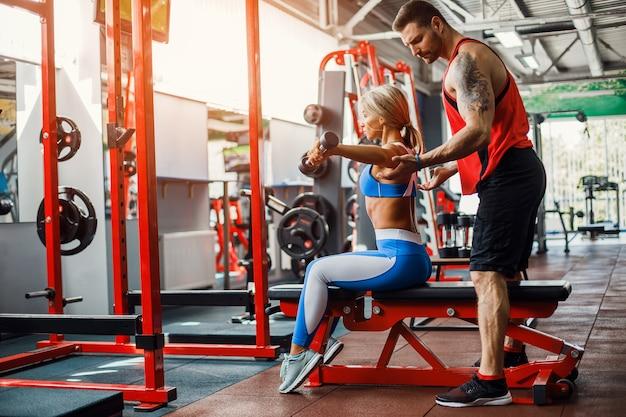 Deportiva mujer haciendo ejercicios con pesas con la ayuda de su entrenador personal en el gimnasio Foto Premium