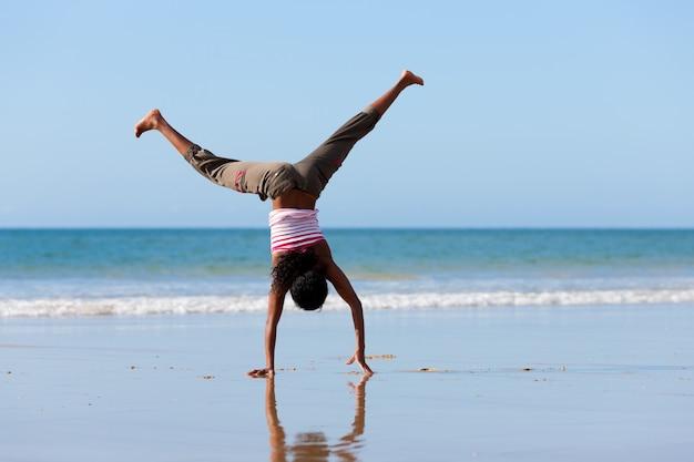 Deportiva mujer haciendo gimnasia en la playa Foto Premium