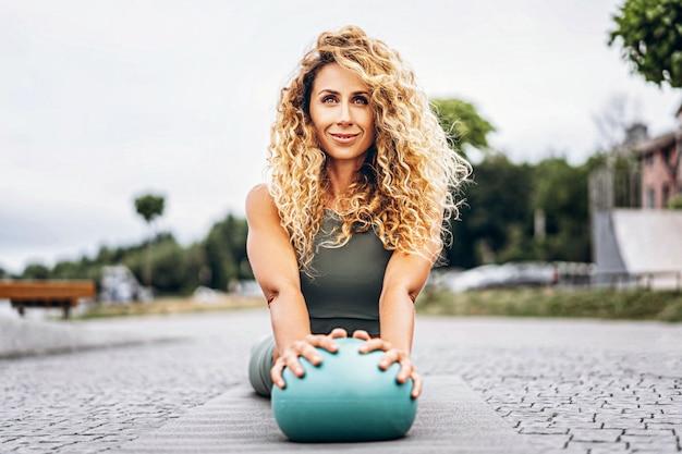 Deportiva mujer joven con pelo largo y rubio y rizado haciendo ejercicios de estiramiento con una pelota especial en la calle. Foto Premium