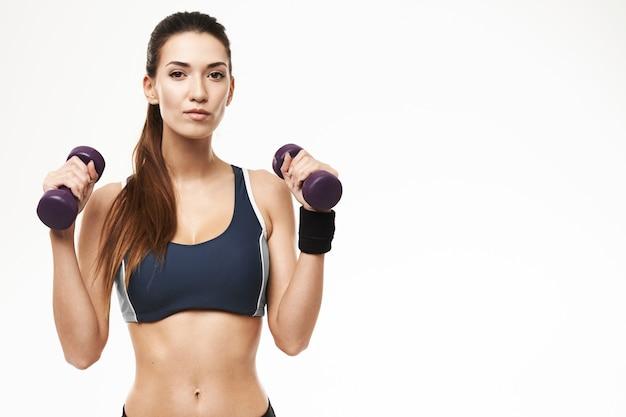 Deportiva mujer con pesas en ropa deportiva posando en blanco. Foto gratis
