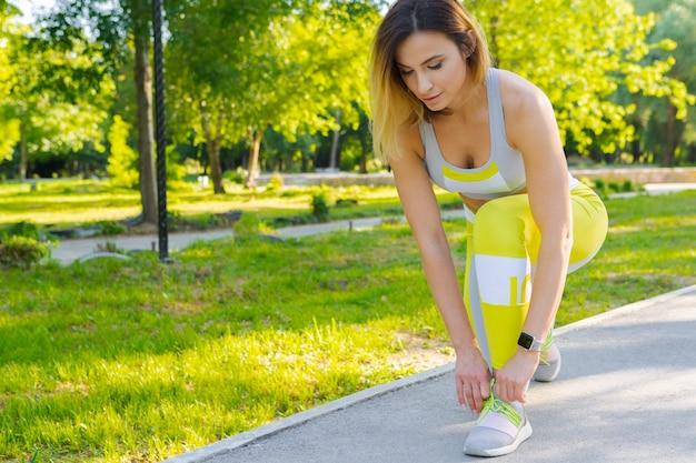 Deportiva mujer en pose de arranque en el parque de la ciudad Foto Premium
