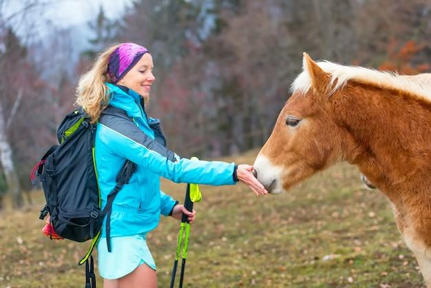 Deportiva niña da hierba para comer un caballo Foto Premium