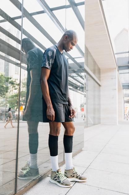 Deportivo joven atleta joven de pie contra el espejo Foto gratis
