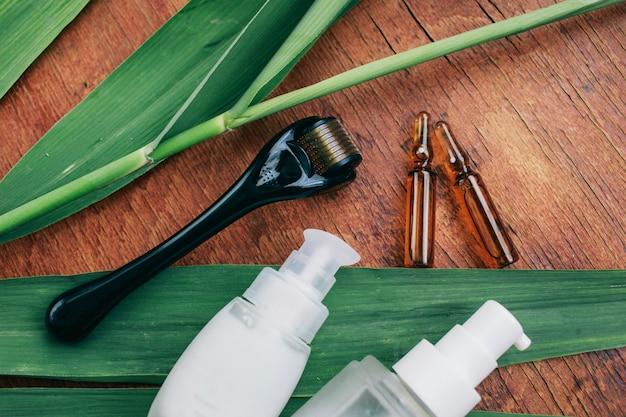 Dermaroller y suero junto a una crema facial antienvejecimiento industria de la belleza primer plano Foto Premium