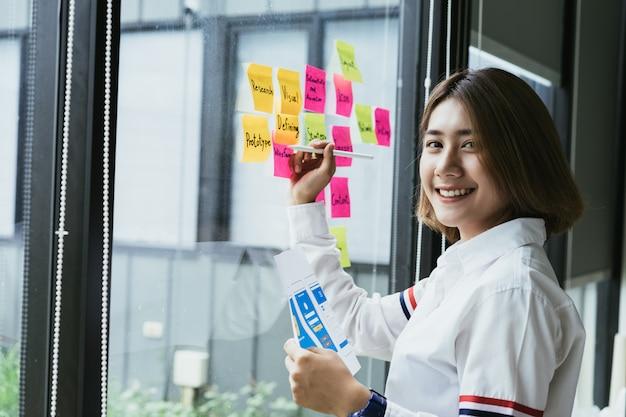 Desarrollador creativo femenino asiático joven de la aplicación móvil que trabaja notas pegajosas coloridas sobre la pared de cristal de la oficina. Foto Premium