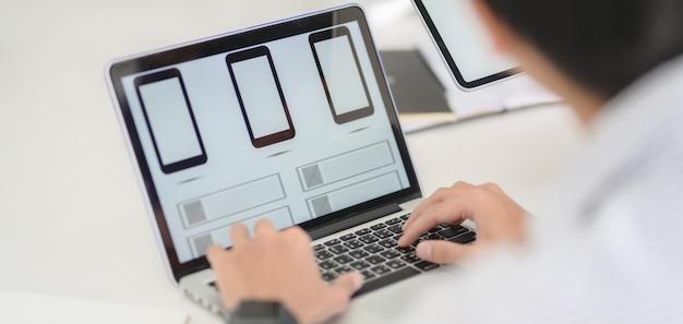 Desarrollador web profesional de ui que trabaja en aplicaciones de teléfonos inteligentes con computadora portátil Foto Premium
