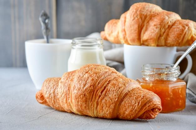 Desayune dos tazas de café con leche, dos cruasanes y mermelada de manzana en un frasco de vidrio. Foto Premium