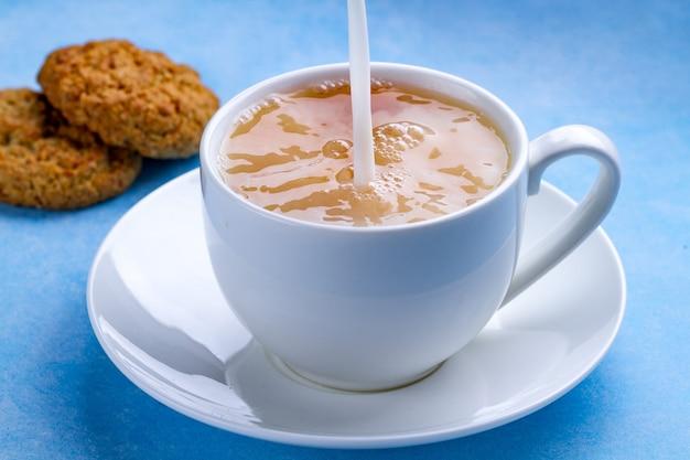 Desayune con galletas de avena y vierta leche en una taza de té negro. harina, postre de cereales y bebida caliente. Foto Premium