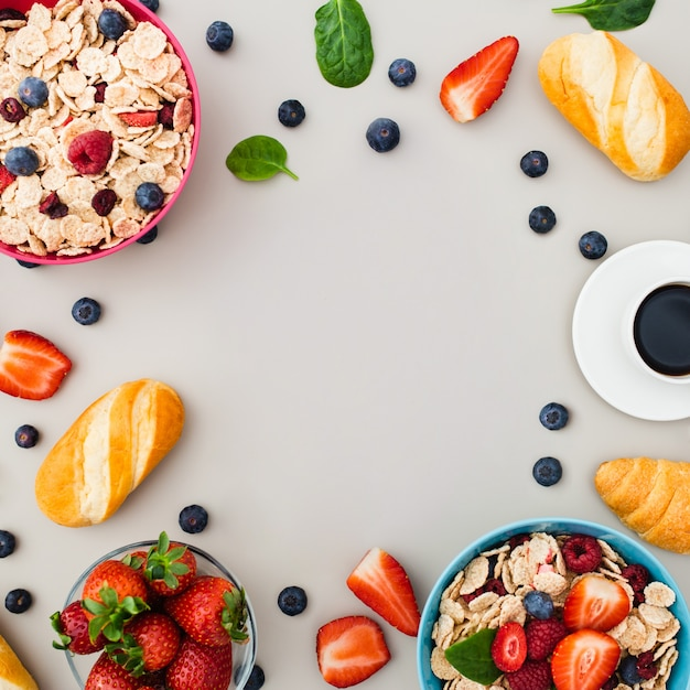 Desayune con el muesli, frutas, bayas, nueces en fondo gris. Foto gratis