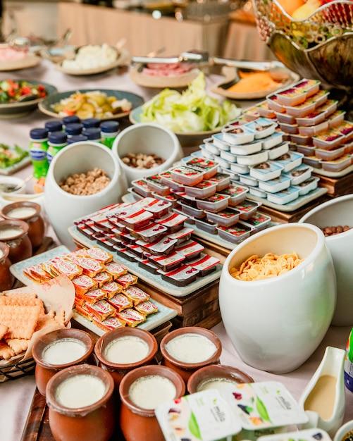 Desayuno buffet con mermeladas de mantequilla, yogures y cereales. Foto gratis
