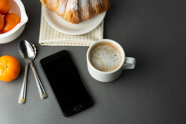 Desayuno café con croissant, cítricos franceses, pastelería, una taza de café o café con leche. la cafeína adicta. Foto Premium