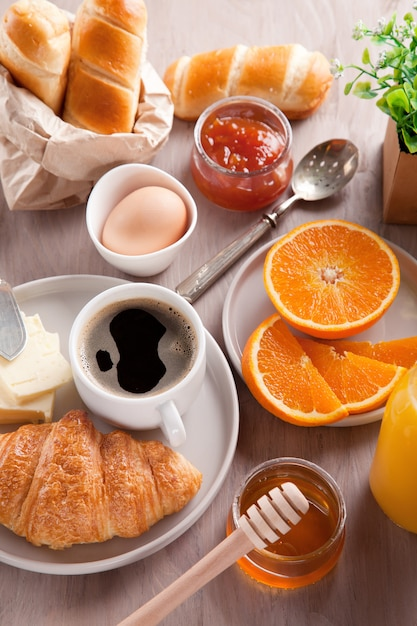 Desayuno con café, zumo de naranja y croissant. vista superior Foto Premium