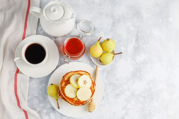 Desayuno casero: tortitas de estilo americano servidas con peras y miel con una taza de té en concreto. vista superior y copia Foto gratis