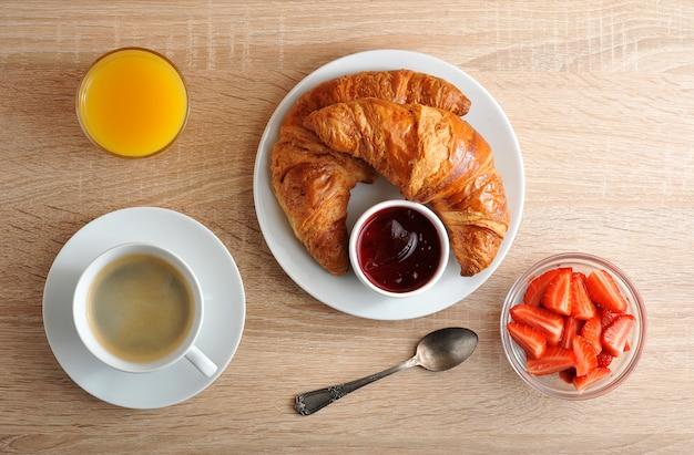 Desayuno continental con café, croissant con mermelada, fresas y jugo de naranja sobre superficie de madera. Foto Premium