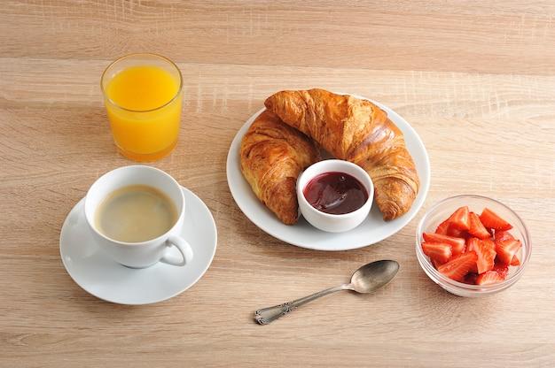 Desayuno continental con café, croissant con mermelada, fresas y jugo de naranja. Foto Premium