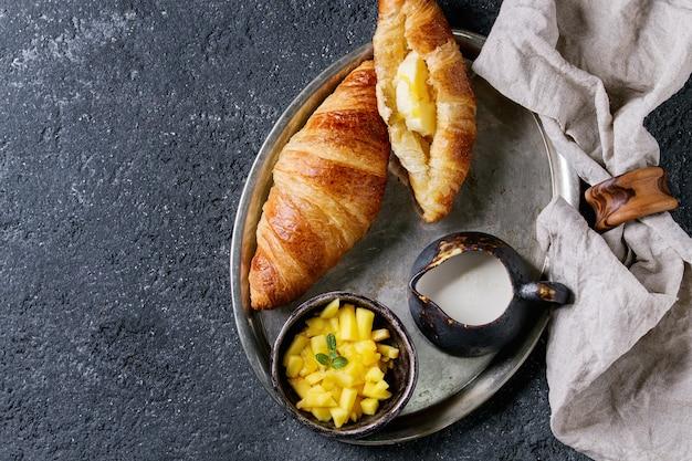Desayuno con croissant y mango. Foto Premium