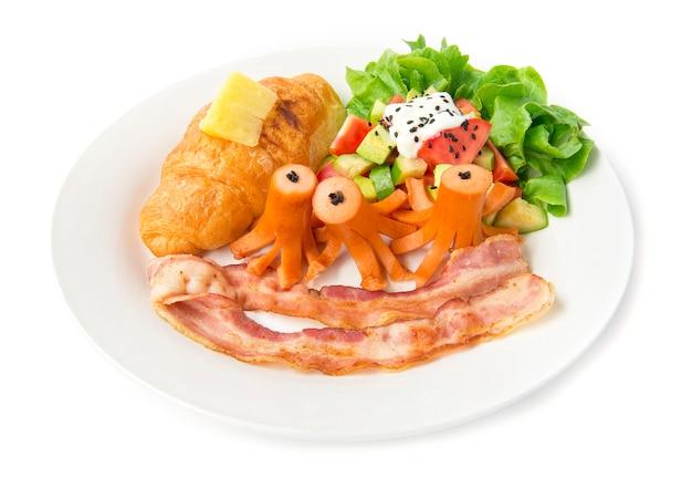 El desayuno con croissant y salchicha de cerdo, tocino y ensalada de aguacate mezcla la verdura en la parte superior del yogur griego espolvorea el sasemi negro y la hoja de roble verde para la vista lateral de la mañana todos los días Foto Premium