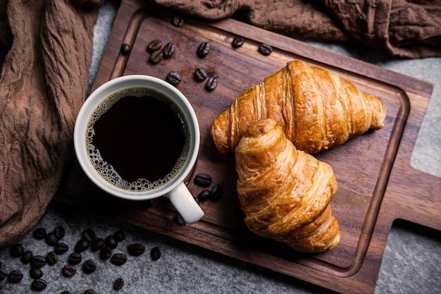Desayuno con cruasanes recién hechos y una taza de café negro sobre tabla de madera Foto Premium