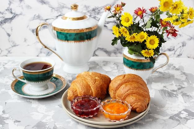 Desayuno francés con cruasanes, mermelada de albaricoque, mermelada de cereza y una taza de té, flores rojas y amarillas. Foto gratis