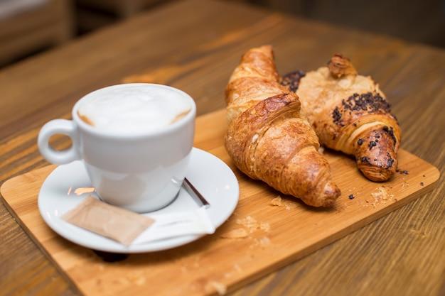 Desayuno francés tradicional con tazas de café caliente y deliciosos croissants frescos colocados en una mesa vintage Foto Premium