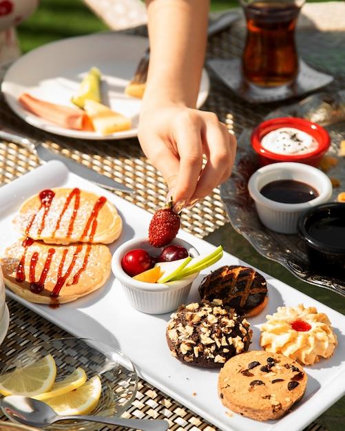 Desayuno con fruta y galletas variadas. Foto gratis