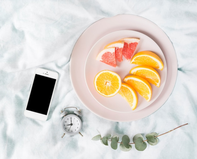 Desayuno con frutas y móvil Foto gratis