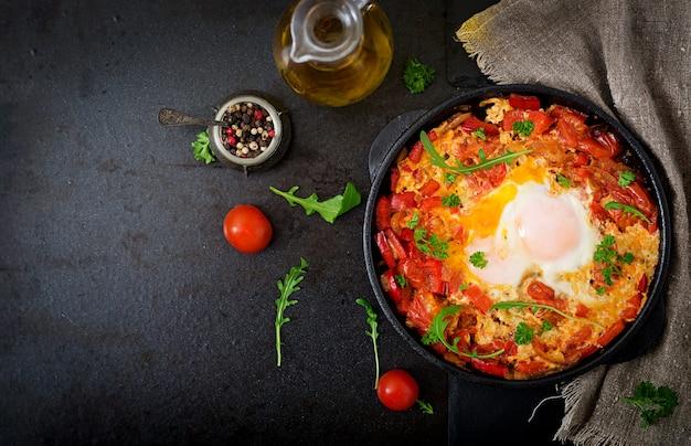 Desayuno. huevos fritos con verduras. shakshuka en una sartén sobre un negro en el estilo turco. Foto gratis