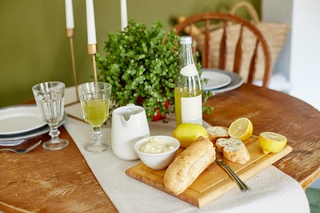 Desayuno de la mañana pan y mantequilla, limonada y limones. una mujer extiende mantequilla sobre pan Foto Premium