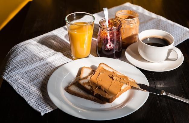 Desayuno con mantequilla de maní y mermelada y una taza de café en una mesa de madera en el sol de la mañana Foto Premium