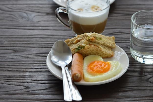 El desayuno en la mesa tiene huevos fritos, salchichas, sándwiches y café. Foto Premium