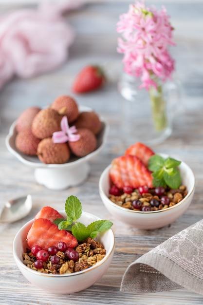 Desayuno de primavera con granola y fresas frescas y lichi y flores sobre fondo de madera. Foto Premium