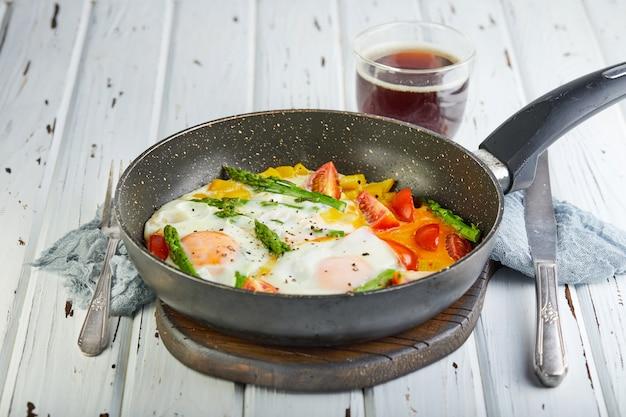 Desayuno sabroso huevos fritos en una sartén con café Foto Premium